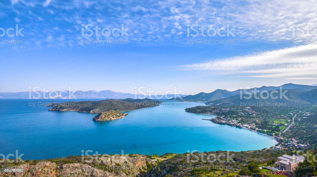 Panoramic view of the gulf of Elounda with  the island of Spinalong and calm sea. Here were isolated lepers, humans with the Hansen's desease and took place the story of Victoria 's Hislop novel 'The Island'. stock photo