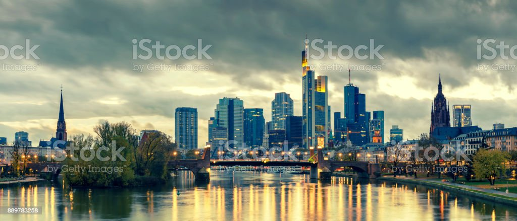 Panoramic view of the illuminated Frankfurt am Main skyline with Alte Brucke and the Dom with moody sky at dusk stock photo