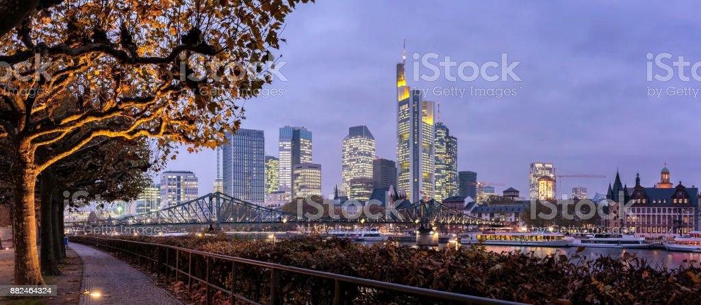 Panoramic view of the illuminated Frankfurt am Main skyline with Eiserner Steg from Schaumankai at dusk stock photo