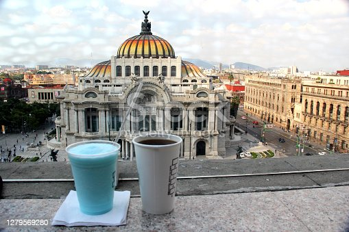 istock panoramic view of the palace of fine arts in mexico city with bird, coffee and blue drink in the foreground 1279569280
