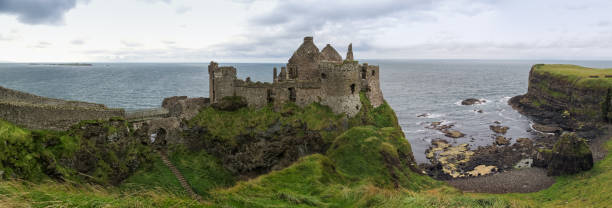 Panoramic view of the ruins of Dunluce Castle and its beach in Northern Ireland stock photo