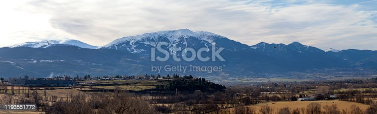 Panoramic view of the snow-capped mountains of Tosa d'Alp or La Tosa, a 2,587-metre-high mountain in Baixa Cerdanya in the Spanish Pyrenees with the Spanish village of Puigcerdà in the foreground.