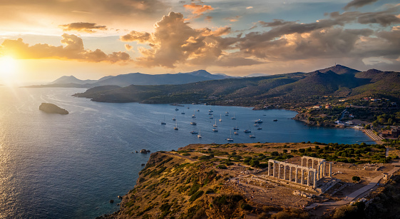 Panoramic view of the Temple of Poseidon at Cape Sounion at the edge of Attica, Greece, with moored sailboats in the bay during sunset time