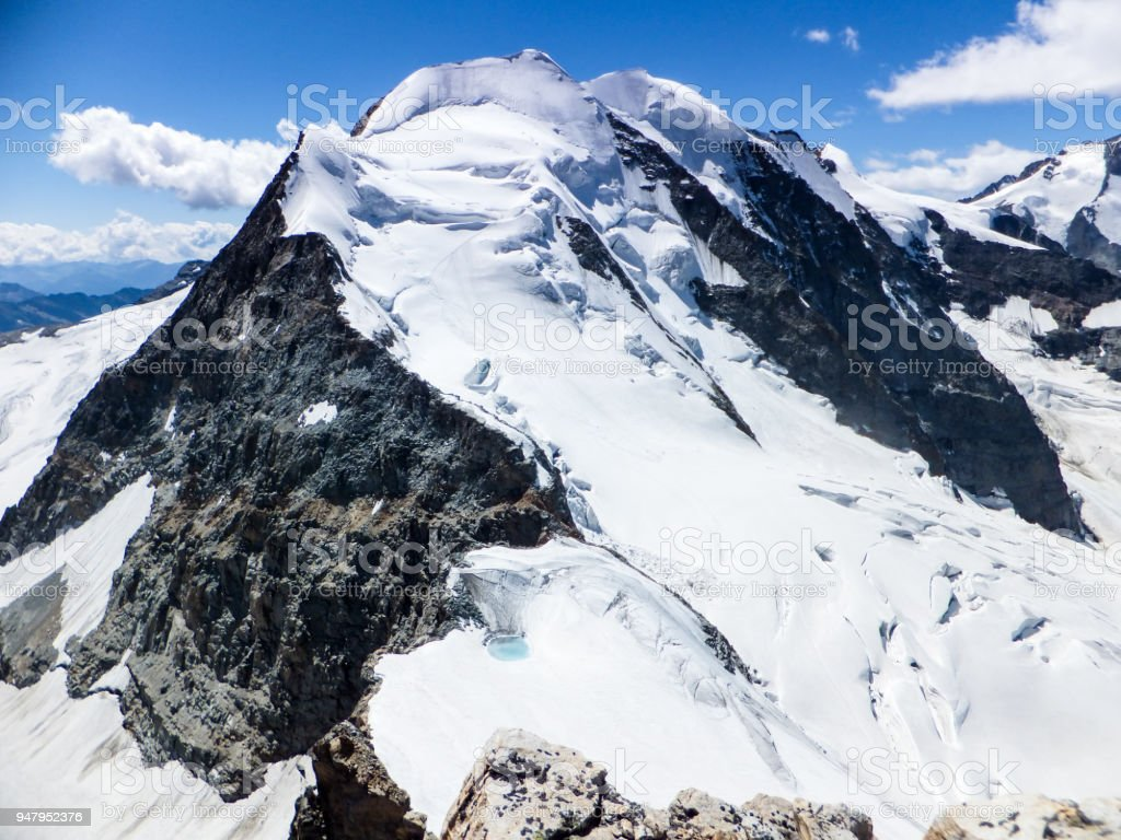 panoramic view of the Val Poschiavo and Piz Palu in the Bernina mountains as seen from the summit of Piz Cambrena stock photo