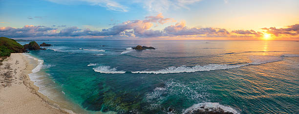 Panoramic view of tropical beach with surfers at sunset. - foto stock