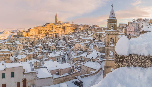 panoramic view of typical stones Sassi di Matera and church of Matera 2019 under blue sky with clouds and snow on the house, concept of travel and christmas holiday,capital of europe culture 2019 panoramic view of typical stones Sassi di Matera and church of Matera 2019 under blue sky with clouds and snow on the house, concept of travel and christmas holiday on snowflakes,capital of europe culture 2019 matera italy stock pictures, royalty-free photos & images