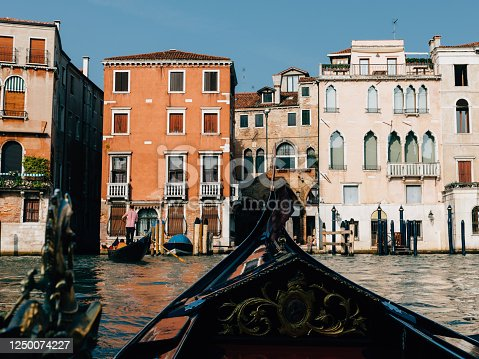Panoramic view of Venice grand canal with historical buildings and gondolas from other gondola. Summer sunny day and sunset sky