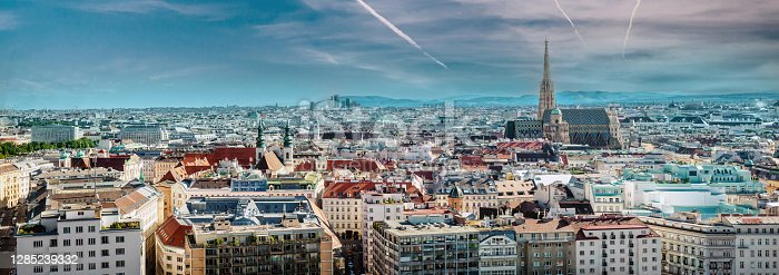 Picturesque view panorama of Vienna city, jet trail in the blue cloudy bright sky, sunny warm day during summertime. European townscape, Austria
