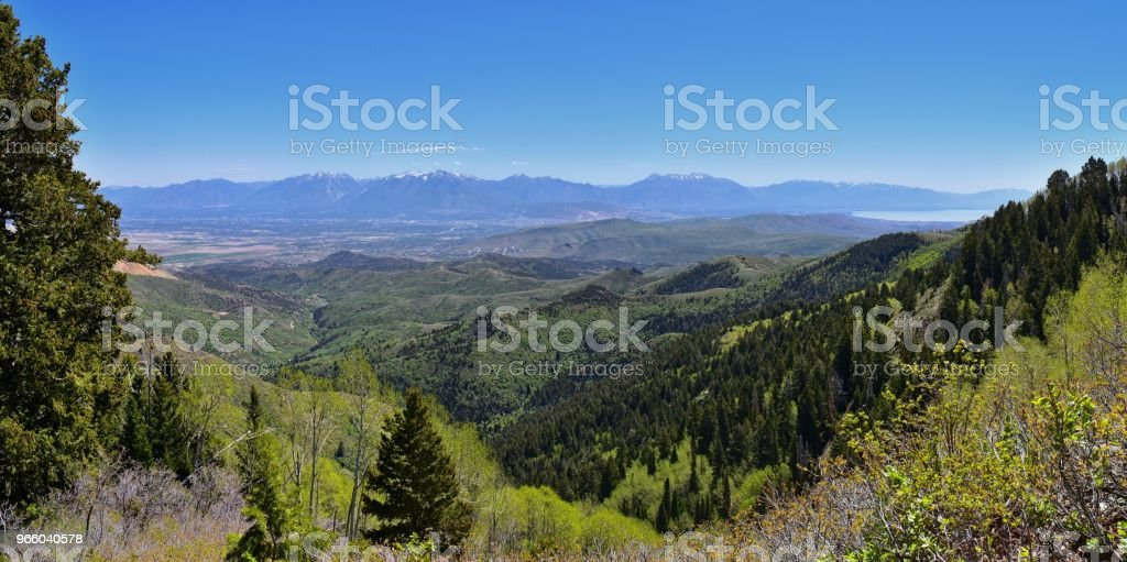 Panoramic view of Wasatch Front Rocky Mountains from the Oquirrh Mountains, by Kennecott Rio Tinto Copper mine, Utah Lake and Great Salt Lake Valley in early spring with melting snow and Cloudscape. Utah, USA. - Стоковые фото Альпайн - Юта роялти-фри