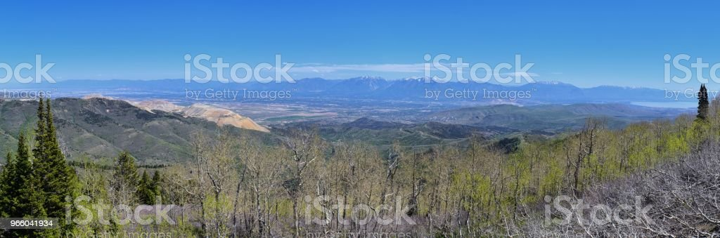 Panoramic view of Wasatch Front Rocky Mountains from the Oquirrh Mountains, by Kennecott Rio Tinto Copper mine, Utah Lake and Great Salt Lake Valley in early spring with melting snow and Cloudscape. Utah, USA. - Royalty-free Alpine - Utah Stock Photo