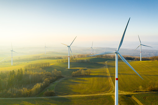 Panoramic view of wind farm or wind park, with high wind turbines for generation electricity with copy space. Green energy concept