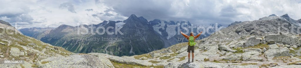 Panoramic view of Young man enjoying freedom in nature, arms outstretched stock photo