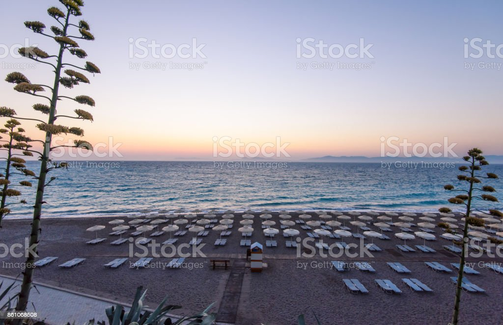 Panoramic view on a comfortable and equipped beach of a beautiful Mediterranean town. Perfect touristic background overlooking the beaches of Rhodes, Greece. stock photo