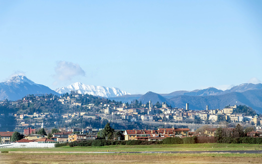 Panoramic view on Bergamo old town in winter sunny day with blue sky from Orio al Serio International Airport