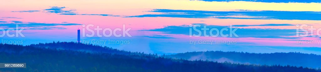 Panoramic view on foggy hilly forest peaks at dusk stock photo