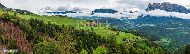 istock Panoramic view on natural Earth Pyramids in Renon, Ritten with medieval church and Alps on background, Italy 1304236941