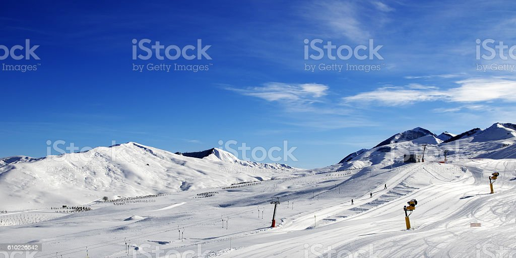 Panoramic view on ski slope with snowmaking at sun day stock photo