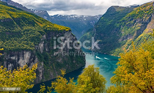 Panoramic view on the mountain ranges in the Geirangerfjord is captured on a summer day. There are mountains around the fjord with turquoise water.