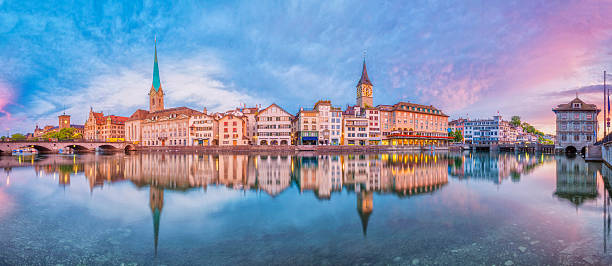 Panoramic view on Zurich at sunrise Panoramic view on Zurich, the river Limmat, Limmatquai, Fraumünster Church (Women's Minster), St. Peter Church and the landmark town hall at sunrise. zurich stock pictures, royalty-free photos & images