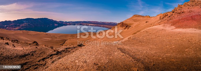 istock Panoramic view over Icelandic landscape of big volcanic caldera Askja, in the middle of volcanic desert in Highlands, with red, turquoise and orange volcano soil at sunset colors, Iceland. 1303909530
