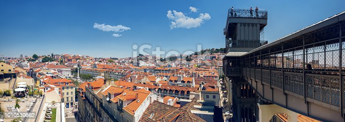 panoramic view over the roofs of historic lisbon with Santa Justa elevator on sunny day