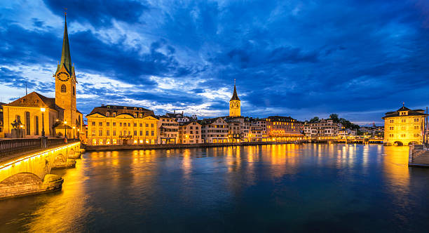 Panoramic view over the Limmat River and Old Town Zürich View over the Limmat River and the old town of Zurich with the landmark Fraumünster church on the left, St. Peter´s church on the Town Hall on the right at dusk. fraumunster stock pictures, royalty-free photos & images