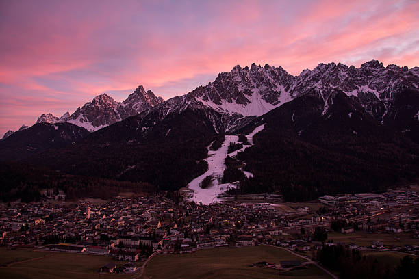 Panoramic view over the village of San Candido at Sunset Panoramic view over the village of San Candido in South Tyrol. Behind the village Dolomites covered with snow. bruneck stock pictures, royalty-free photos & images