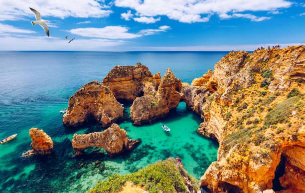 Panoramablick, Ponta da Piedade mit Möwen, die über Felsen in der Nähe von Lagos in der Algarve, Portugal. Klippen Felsen, Möwen und Touristenboot auf dem Meer in Ponta da Piedade, Algarve Region, Portugal. – Foto