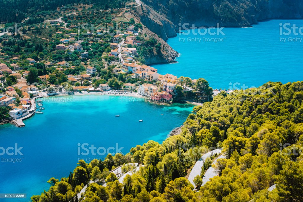 Panoramic view to Assos village Kefalonia. Greece. White lonely yacht in beautiful turquoise colored bay lagoon water surrounded by pine and cypress trees along the coastline stock photo