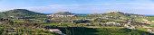Panoramic view to Corpus Christi Parish Church,\nGordan Lighthouse and fields. Malta. Gozo.