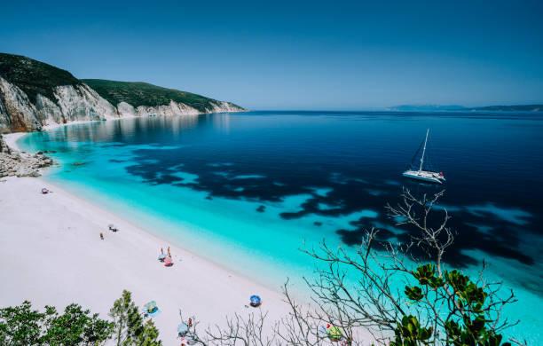 바다 물 처럼 맑고 푸른 카리브해에서 외로운 흰색 뗏목 요트 드리프트로 원격 해변 파노라마 보기 푸른 색된 얕은 산호초와 해변에서 관광객의 여가 활동 - 이오니아 해 뉴스 사진 이미지