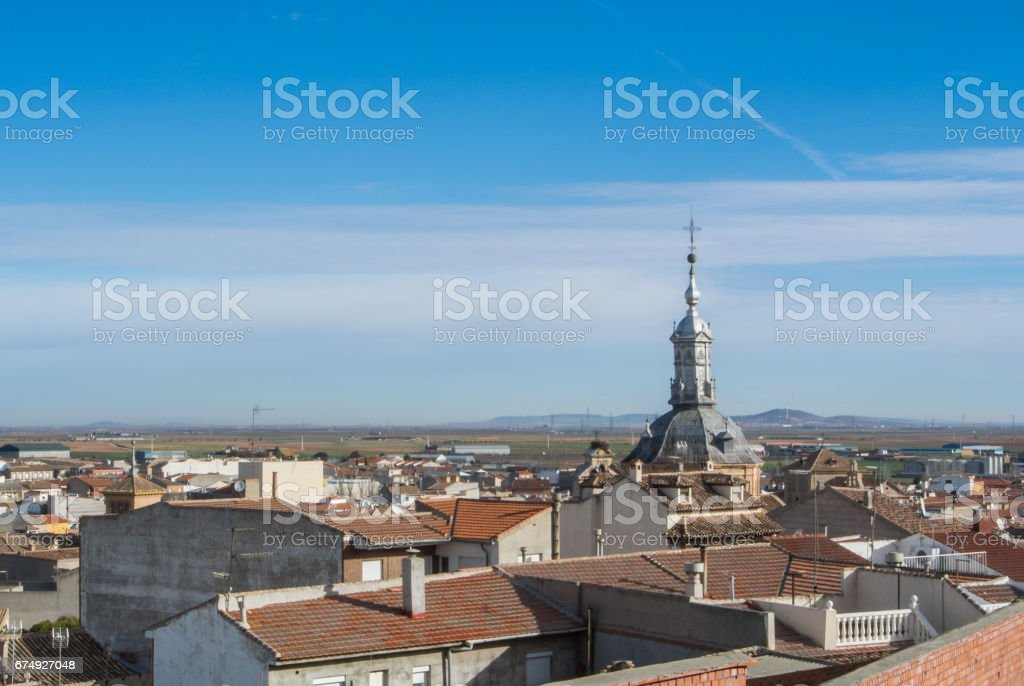 A panoramic view to spanish town Consuegra (Castilla-La Mancha) and a church over the orange tile roofs on sunny day. royalty-free stock photo