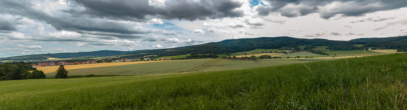 Panoramic view to summer Czech landscape with small vilage Chlum and hill Klet at dramatic cloudy sky