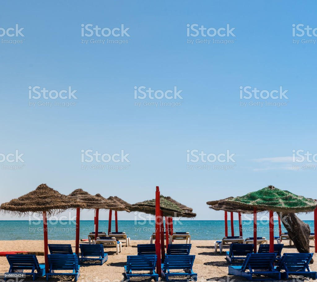 Panoramic view to the wild sandy Isla beach with seascape and gold sand. Straw and wooden sun umbrellas and sunbeds standing on the shore stock photo