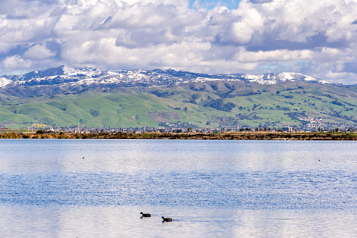 istock Panoramic view towards green hills and snowy mountains on a cold winter day taken from the shores of a pond in south San Francisco bay area; San Jose, California 1127818376