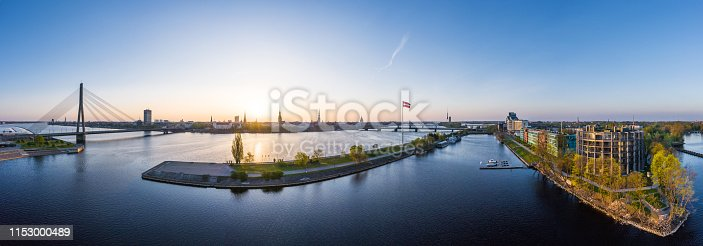Panoramic view towards river Daugava at sunrise. In foreground AB dam can be seen. And in the background there's the beautiful Old Riga city lights. On left is Kliversala district.