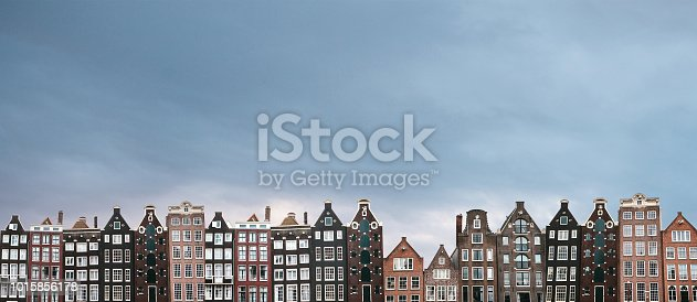 Panorama or panoramic view. Traditional houses in Amsterdam in the Netherlands in a row against the backdrop of the setting sun.