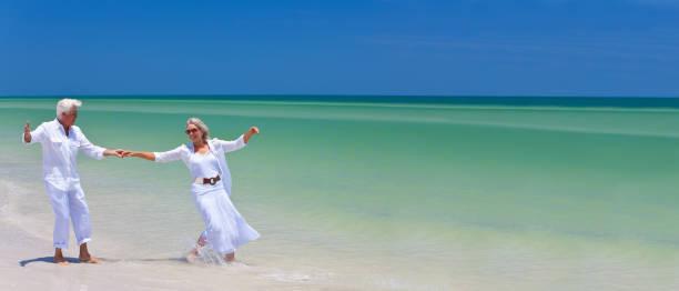 Web panorámicas banner senior hombre y mujer pareja feliz bailando y cogidos de la mano en una playa tropical desierta con cielo azul brillante - foto de stock