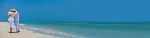 Pancarta de la web panorámica feliz hombre mayor y mujer pareja bailando en una playa tropical desierta con panorama azul claro brillante del cielo - foto de stock