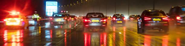 Panorámica web banner movimiento borrosa fotografía de tráfico en la noche bajo la lluvia en una autopista británica con el oficial de policía y el coche - foto de stock