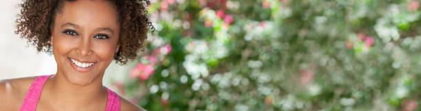 Pancarta panorámica de hermosa joven sonriendo raza mixta biracial negro mujer afroamericana haciendo ejercicio al aire libre con un fondo floral natural. Imagen de encabezado panorámico. - foto de stock