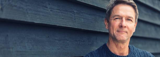 Retrato pancarta de la web panorámica foto de un hombre de mediana edad atractivo, exitoso y feliz hombre de mediana edad fuera con un panorama de suéter azul - foto de stock