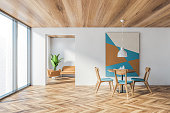 Interior of stylish panoramic dining room with white walls, wooden floor, round table with blue chairs and abstract picture and living room with beige sofa in background. 3d rendering