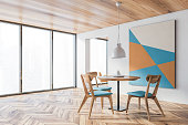 Corner of spacious panoramic dining room with white walls, wooden floor, round table with blue chairs and abstract picture and window with blurry cityscape. 3d rendering