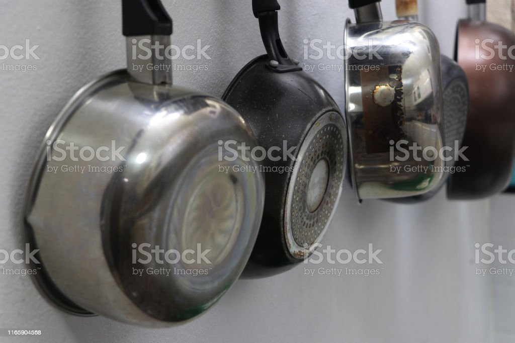 Pans and pots for cooking, hanging in the kitchen. Pans and pots for cooking, hanging in the kitchen. Chrome Stock Photo