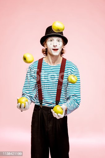 istock Pantomime juggling with apples on the pink background 1138421199