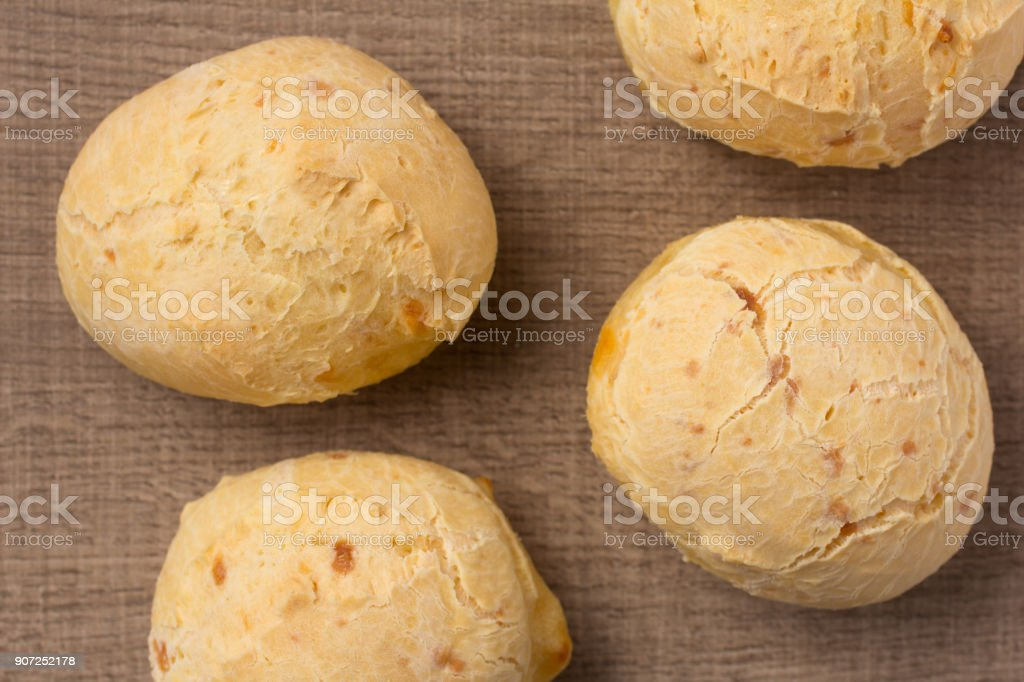 Pao de Queijo is a cheese bread ball from Brazil. Also known as Chipa, Pandebono and Pan de Yuca. Snacks on wood table, flat lay design. stock photo