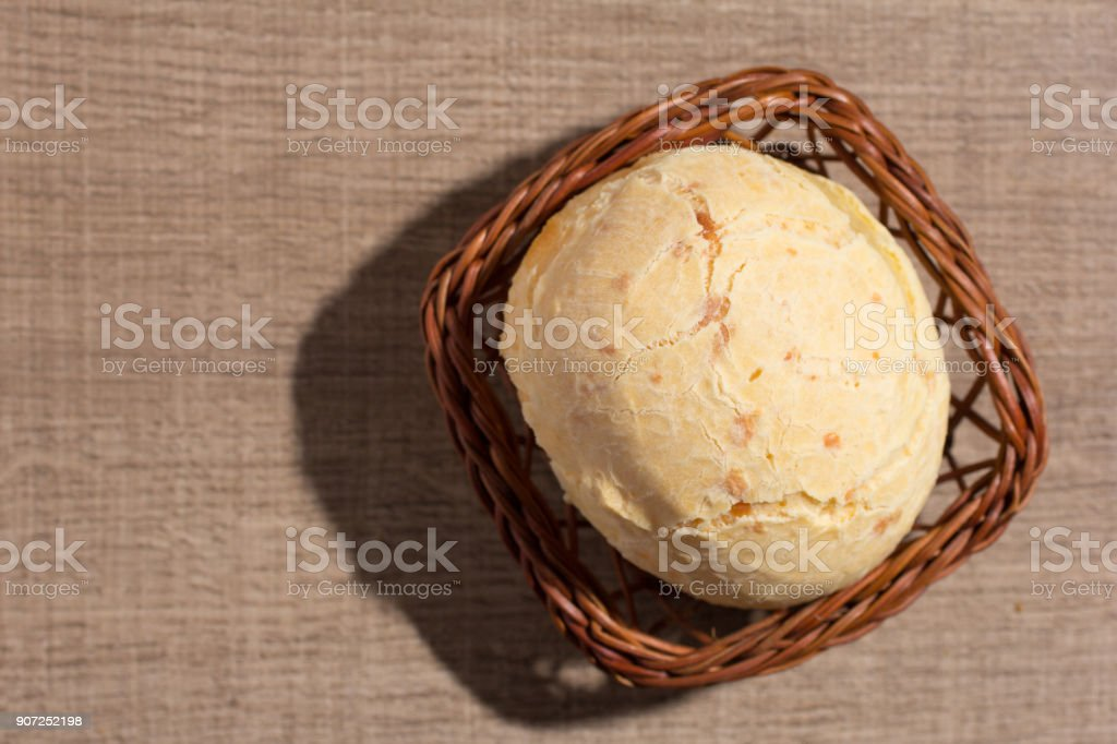 Pao de Queijo is a cheese bread ball from Brazil. Also known as Chipa, Pandebono and Pan de Yuca. One snack in basket over wood table, flat lay. stock photo