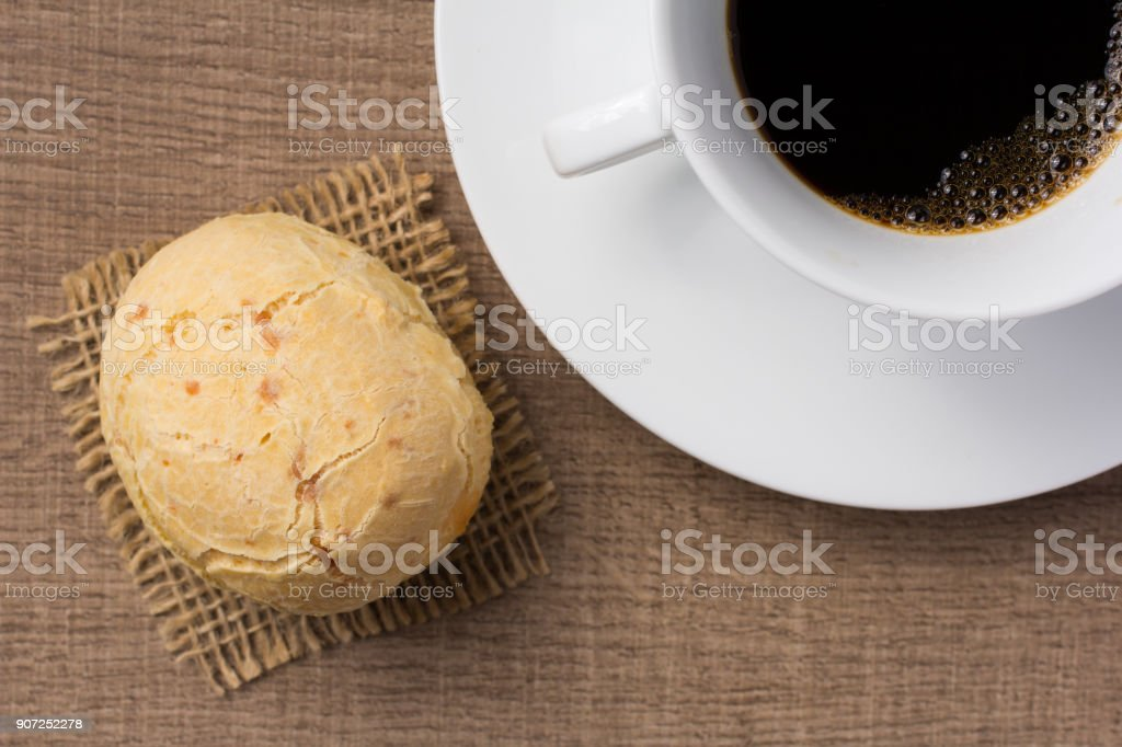 Pao de Queijo is a cheese bread ball from Brazil. Also known as Chipa, Pandebono and Pan de Yuca. Snack and cup of coffee on wood, overhead. stock photo