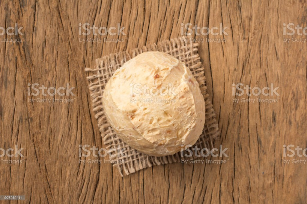 Pao de Queijo is a cheese bread ball from Brazil. Also known as Chipa, Pandebono and Pan de Yuca. One snack on rustic wood table, top view. stock photo
